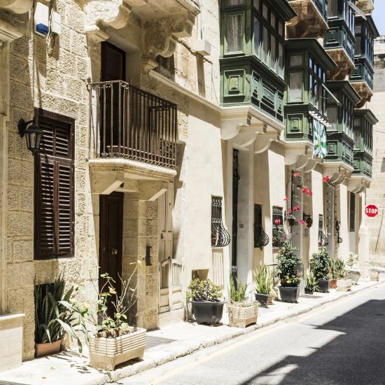 Typical narrow street on the island of Malta. Buildings with traditional colorful maltese balconies in historical part of Valletta.